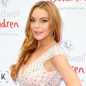 Swimsuit-Clad Lindsay Lohan Bonds with Nature Puckering Up to a Cute Fish