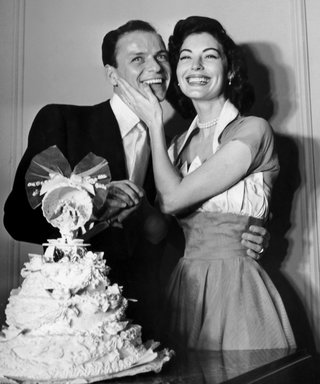 7th November 1951:  American pop singer Frank Sinatra poses with his wife, American actor Ava Gardner, standing behind their wedding cake on their wedding day. Gardner holds her hand on Sinatra's cheek.  (Photo by Hulton Archive/Getty Images)