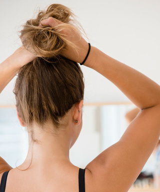 Mixed race dancer tying hair in bun