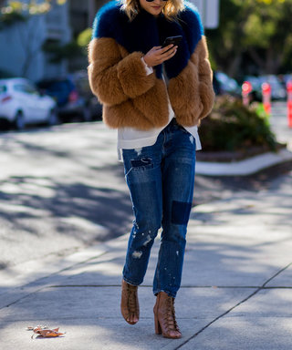 A guest wearing a navy brown fur coat, navy blue denim jeans with patches and peep toe heels at Mercedes-Benz Fashion Week Resort 17 Collections at Carriageworks on May 20, 2016 in Sydney, Australia.