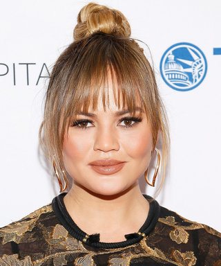 Chrissy Teigen Cradles Her Baby Bump in a White Cutout Swimsuit