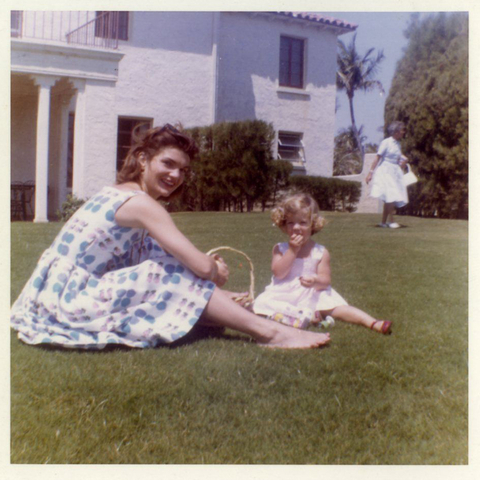 Jackie Kennedy having a picnic with Carolyn Kennedy on the lawn.