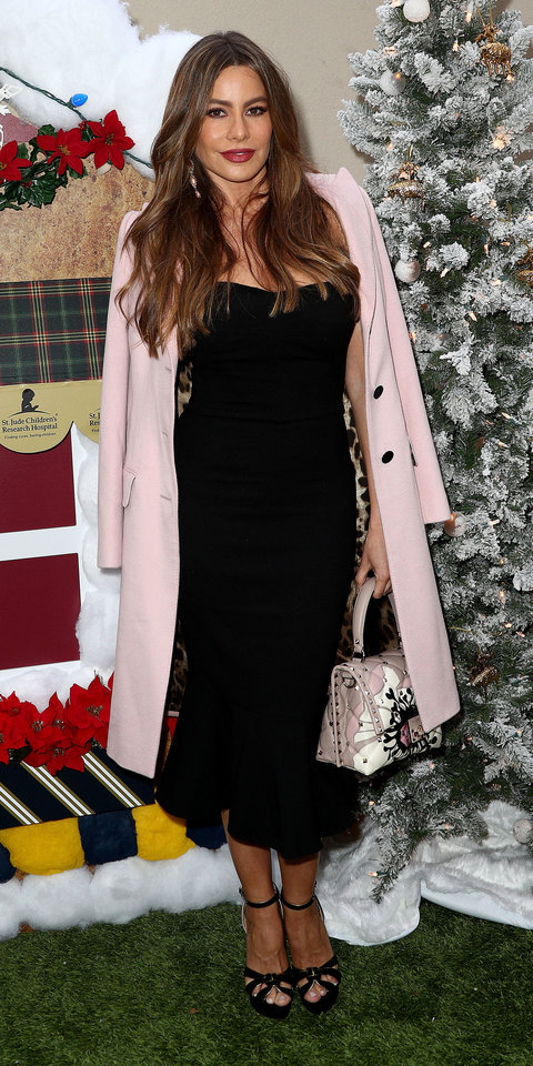 During a Brooks Brothers holiday party, Sofia Vergara stepped out in a sleek black dress and heels, which were brought to life with a pink coat and a coordinating handbag.