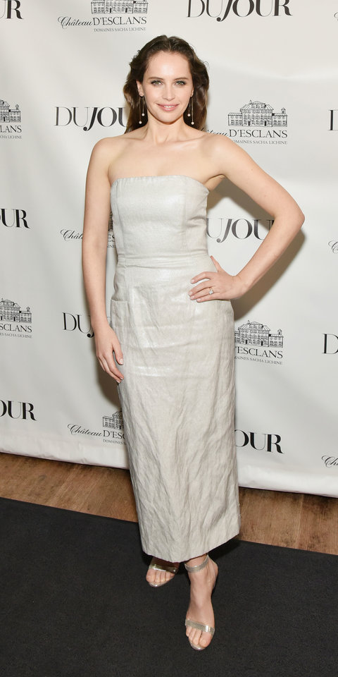 While celebrating her cover on Dujour , Felicity Jones rocked a strapless sheath dress with metallic heels and sparkly drop earrings.