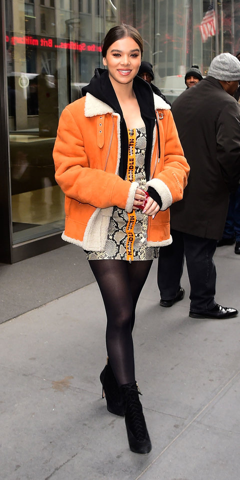 Hailee Steinfeld made a bright statement in an orange Heron Preston coat, python mini dress, black tights, and boots.