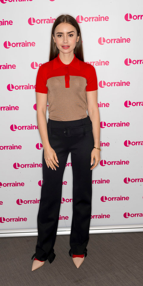 Lily Collins mixed in pops of red into a neutral look for an appearance on the Lorraine TV show in London.