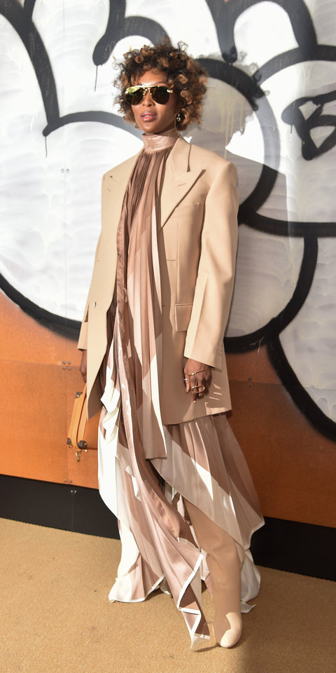 Naomi Campbell attended the Louis Vuitton men's presentation in a pleated dress and beige knee-high boots, which matched her long-line blazer.