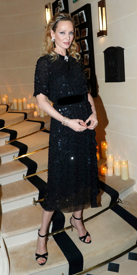 Uma Thurman nailed cocktail dressing in a belted Prada dress with large sequins, a coordinating headband, dangling earrings, and criss-cross sandals.