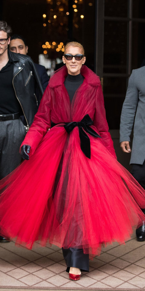 Celine Dion brought an all-black outfit to life by topping it off with a red tulle coat by Oscar de la Renta and shiny Alexandre Vauthier pumps .