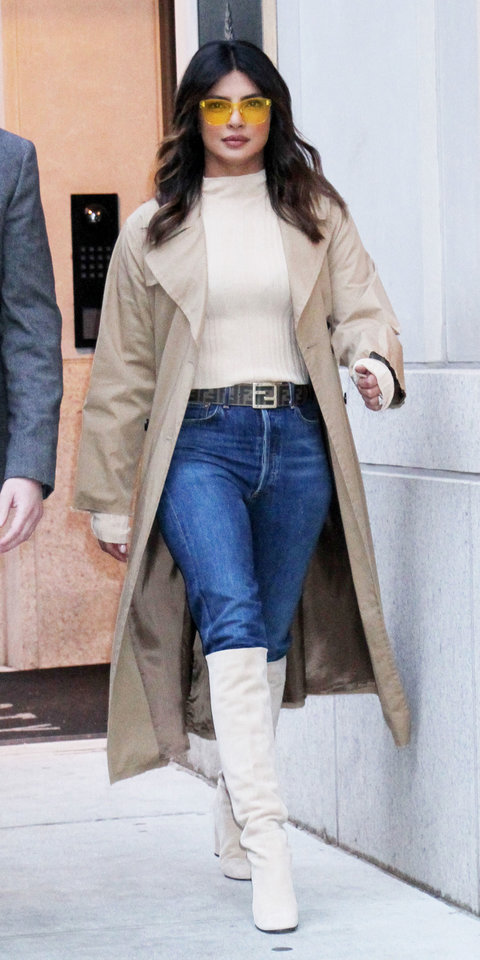 During a casual outing, Priyanka Chopra put together a cool outfit with a beige top tucked into blue jeans and a Fendi belt . Stuart Weitzman boots ($535; mytheresa.com ), a khaki coat, and yellow sunglasses solidified her winning outfit.