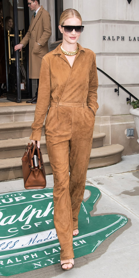Rosie Huntington-Whiteley made a cool statement in a suede jumpsuit, bronze Jimmy Choo heels, chunky necklace, ombré sunglasses, and a top handle bag.
