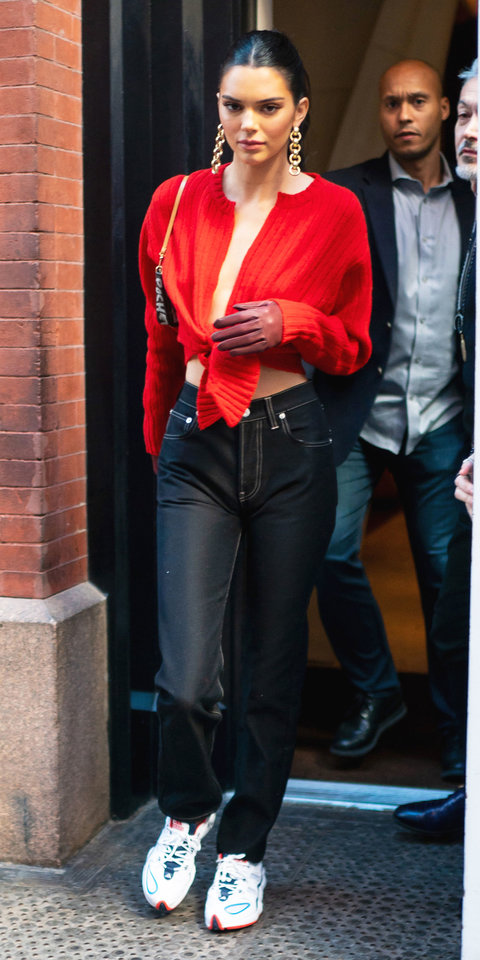 Kendall Jenner dressed up a pair of cool jeans and sneakers with a tied-up red blouse, burgundy gloves, and gold earrings.