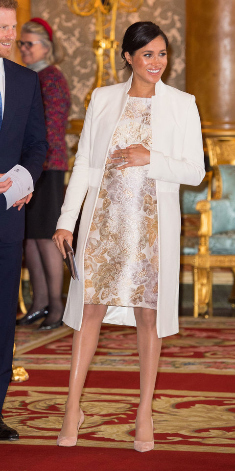 During a celebration at Buckingham Palace, Meghan Markle layered a beige Amanda Wakely coat ($1,190; orchardmile.com ) over a brocade dress and finished off her look with Paul Andrew pumps ($745; barneys.com ).