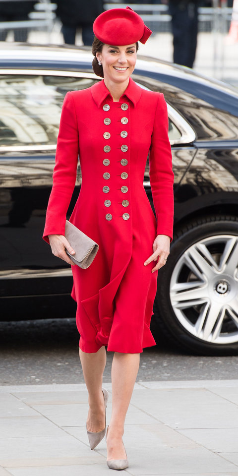 Kate Middleton made a glam statement in a red Catherine Walker coat dress with a plethora of buttons. Emmy London heels , a matching bag , and a beautiful fascinator completed her outfit.