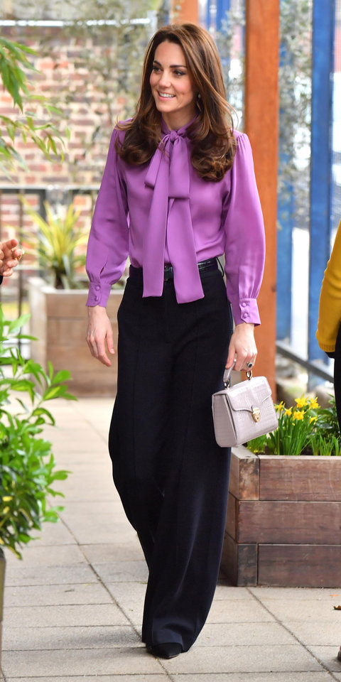 Kate Middleton gave her usual A-line dresses a break and stepped out in a Gucci blouse ($1,300; neimanmarcus.com ), trendy wide-leg pants, and her favorite Aspinal of London bag ($725; orchardmile.com ).