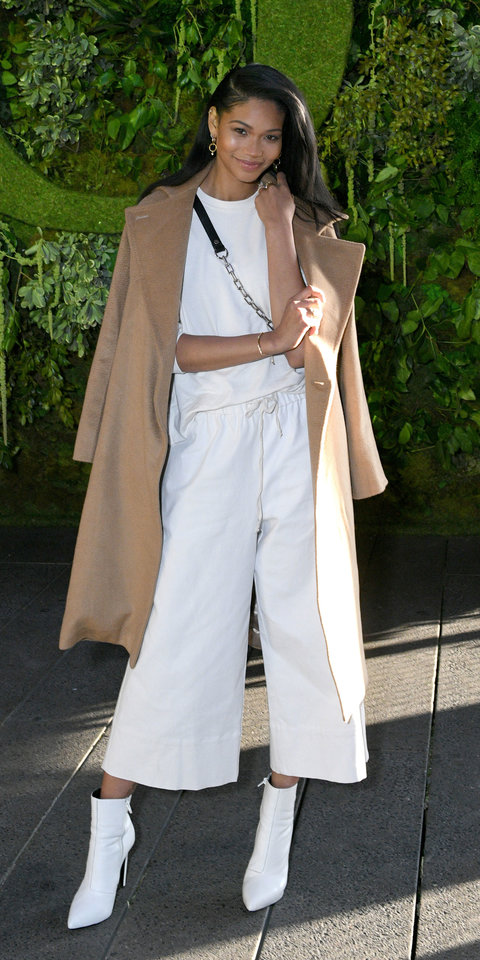Chanel Iman celebrated the launch of Pandora's Garden collection in comfy, cropped trousers, white T-shirt, pointed-toe boots, Pandora jewels, and a camel coat.