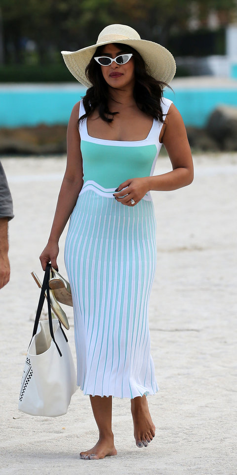 Priyanka Chopra served up vacation goals in a Ph5 dress ($385; ph5.com ), cat-eye sunglasses, a straw hat, and Brian Atwood flats while in Miami.