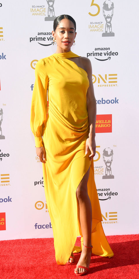 Laura Harrier lit up the scene at the NAACP Awards in a one-shoulder Pyer Moss gown, red sandals, and gold earrings.
