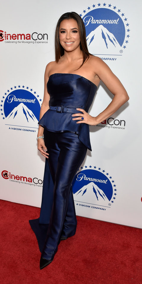 Eva Longoria attended CinemaCon in a Vitor Zerbinato jumpsuit, Nigora Tabayer jewels, and Victoria Beckham shoes.