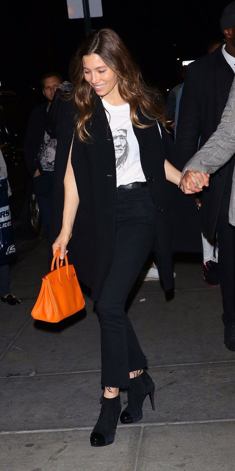 Jessica Biel stepped out for Dwyane Wade's retirement party in a graphic T-shirt, black swing coat, coordinating skinny jeans, suede boots, and an orange Hermès bag ($17,115; farfetch.com ).