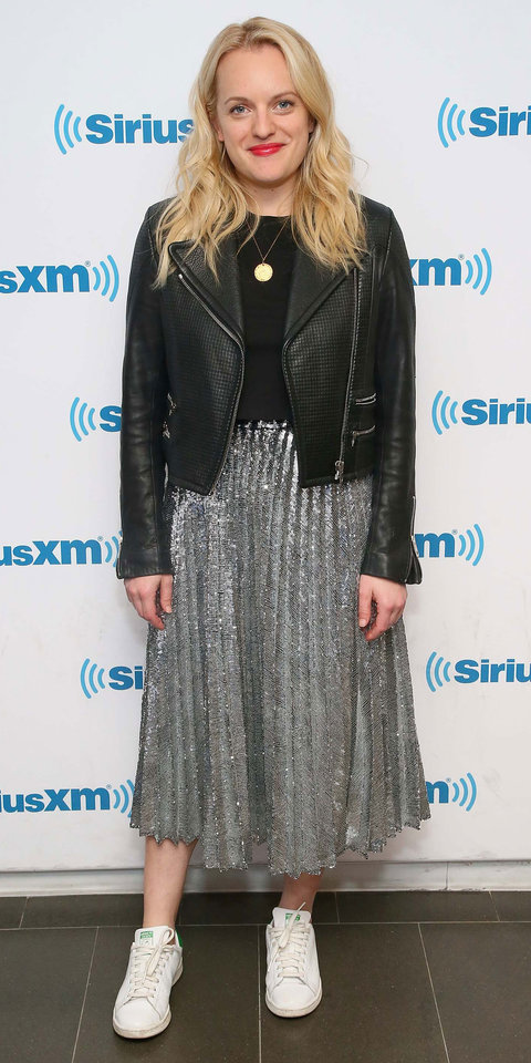 While visiting SiriusXM Studios in NYC, Elisabeth Moss balanced out her metallic midi skirt with some classic wardrobe staples, including a black leather jacket, a black tee, and some Adidas Stan Smith sneakers.