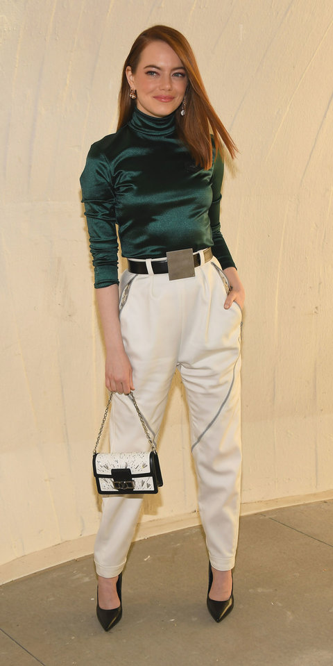 Emma Stone attended the Louis Vuitton Cruise 2020 show in a emerald turtleneck tucked into white strousers.