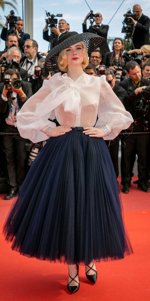 Elle Fanning brought an extra dose of glam to the Cannes red carpet in Christian Dior sheer blouse, flare skirt, black hat, and criss-cross pumps.