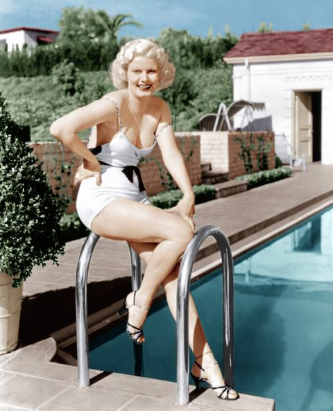 Jean Harlow in white swimsuit and heels in front of pool