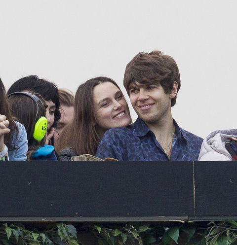 EXCLUSIVE: Keira Knightley and James Righton look loved-up as they hide from the rain while watching the Blur concert at Hyde Park in London
