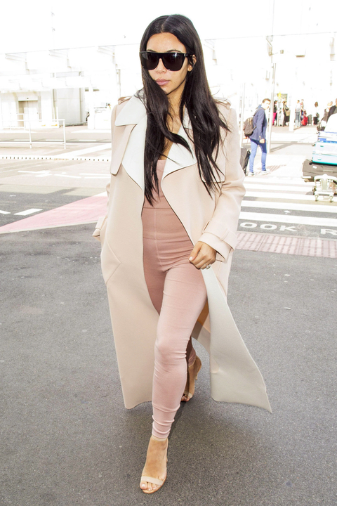 Pregnant Kim Kardashian catches a flight out of Heathrow Airport on June 29, 2015 in London, England. The reality star, dressed in a tight pink jumpsuit, a long cream coat and cream heels, spent the weekend watching her husband Kanye West perform at the G
