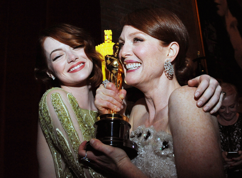 Nominee for Best Supporting Actress Emma Stone (L) embraces Winner for Best Actress Julianne Moore at the Governor's Ball following the 87th Oscars February 22, 2015 in Hollywood, California.