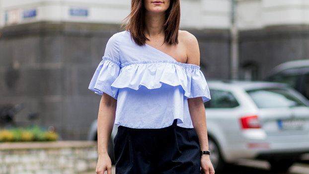COLOGNE GERMANY - APRIL 13: Fashion blogger Golestaneh Mayer-Uellner wearing blue sleveless blouse from Zara, black wide pants from Kenzo, beige Celine bag, Celine sunglasses, red Valentino shoes on April 13, 2016 in Cologne, Germany