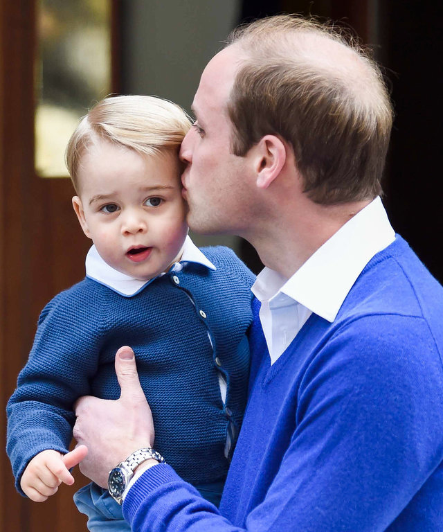 Prince William, Duke of Cambridge kisses Prince George of Cambridge as they arrive at the Lindo Wing following the birth his second child on May 2, 2015 in London, England.