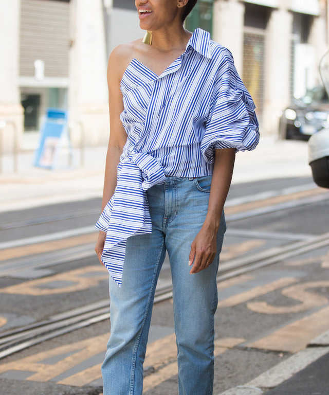 MILAN, ITALY - JUNE 19:  Tamu McPherson wears a blue and white Johanna Ortiz off-the-shoulder ruffle top with jeans and white mules during the Milan Men's Fashion Week Spring/Summer 2017 on June 19, 2016 in Milan, Italy.  (Photo by Melodie Jeng/Getty Imag