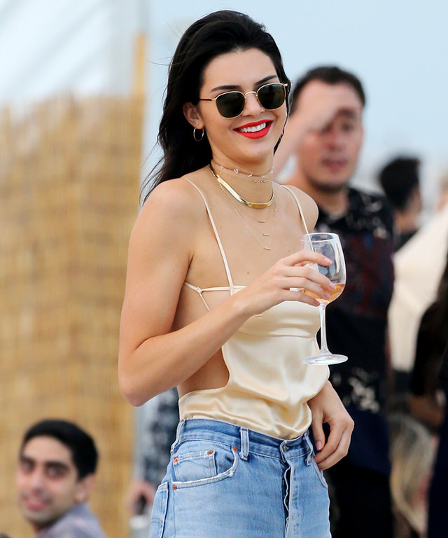 December 4, 2016: Kendall Jenner wears a revealing strappy top and jeans as she enjoys a glass of wine on the beach in Miami. Mandatory Credit: INSTARimages
