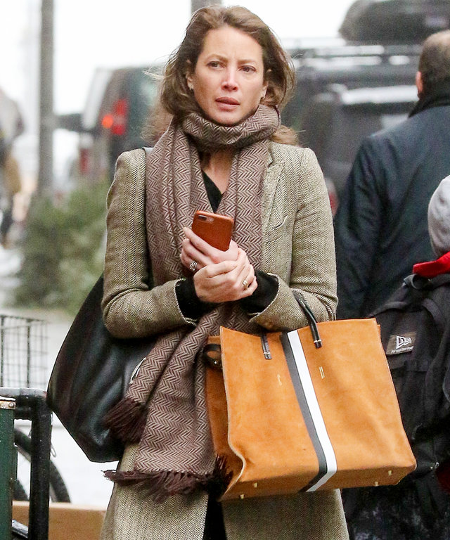 New York, NY - Christy Turlington grabs a seat and checks out her messages on her phone while waiting for the subway train during her commute today.