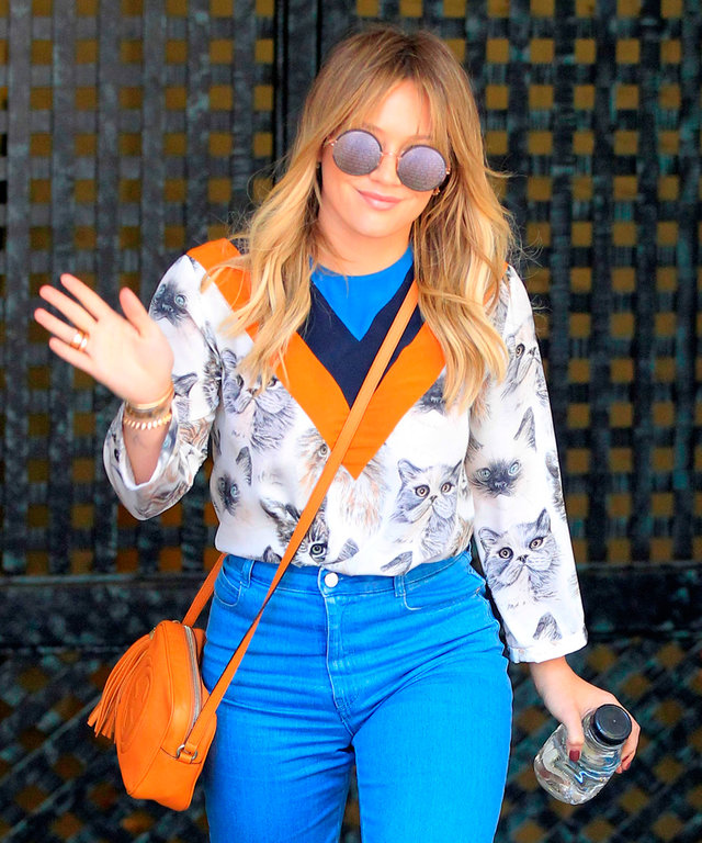 Actress, Hilary Duff, looks retro in a kitty printed blouse, two-tone pants, camel handbag, round mirrored sunglasses, and suede shoes while shopping in Beverly Hills.
