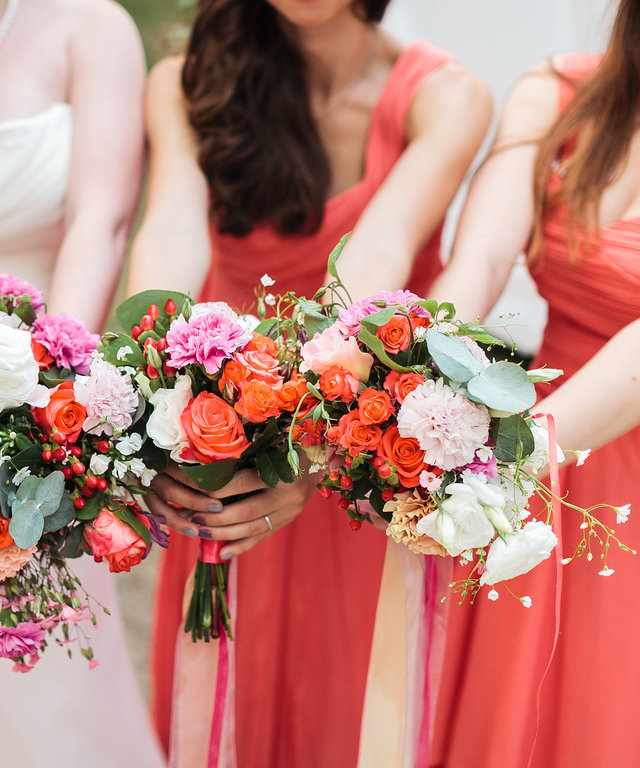 Bridesmaids and bride holds bouquets in hand.
