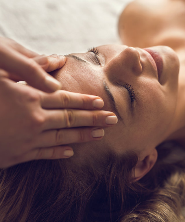 Mid adult woman enjoying in her relaxing head massage at the spa.