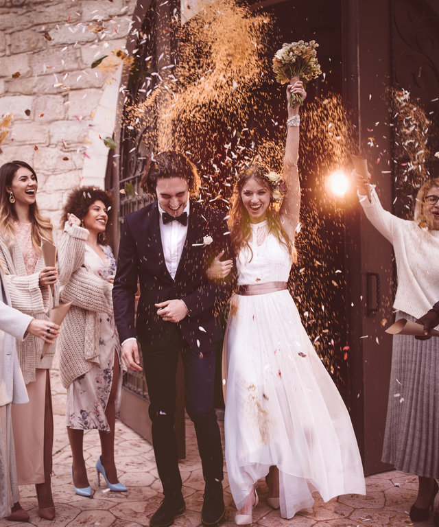 Newlywed couple walking out church and celebrating wedding with confetti