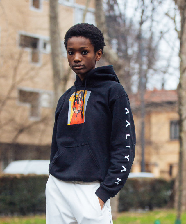 Model Imari Karanja wears a black Aaliyah hoodie, white Tory Burch button pants, and white chunky disruptor Fila sneakers during Milan Fashion Week Fall/Winter 2018/19 on February 22, 2018 in Milan, Italy.  (Photo by Melodie Jeng/Getty Images)