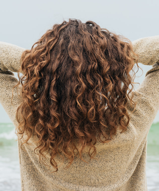 Curly brunette in a sweater on the coast