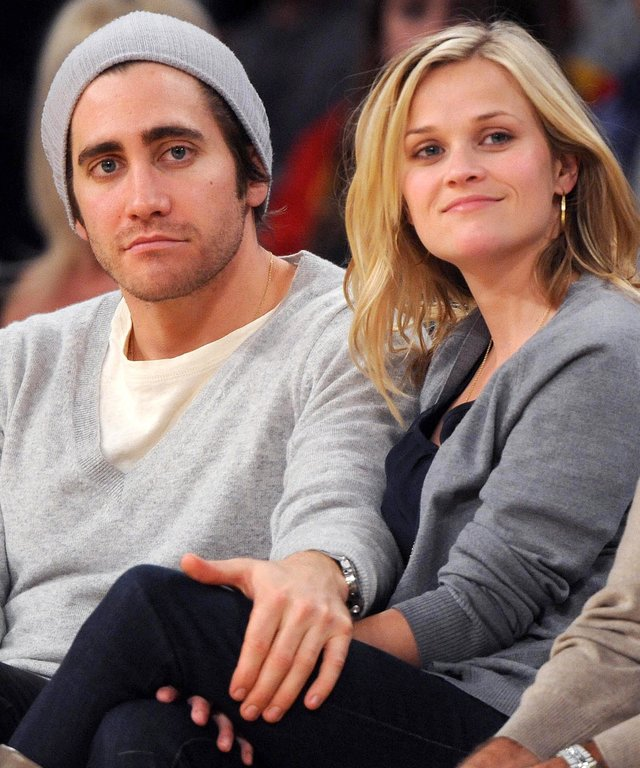 Actors Jake Gyllenhaal and Reese Witherspoon sit courtside