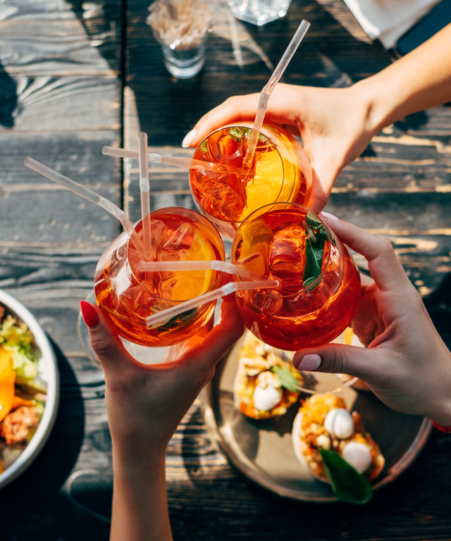 Overhead view of three women making a celebratory toast with aperol spritz cocktails