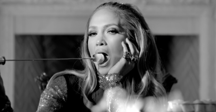 J. Lo roasts a marshmallow on a pile of burning money