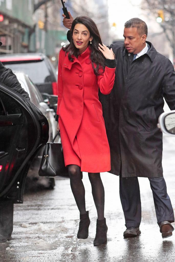 EXCLUSIVE: Amal Alamuddin Clooney wears a red coat while navigating the snow storm in New York City