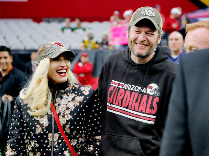 Singers Gwen Stephani and Blake Shelton stand on the sidelines prior to an NFL football game between the Green Bay Packers and the Arizona Cardinals, Sunday, Dec. 27, 2015, in Glendale, Ariz.