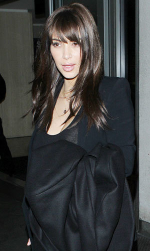 Kim Kardashian rocks a new side-swept fringe and dark hair colour