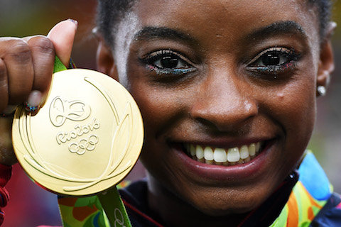 RIO DE JANEIRO, BRAZIL - AUGUST 09:  Simone Biles of the United States poses for photographs with her gold medal after the medal ceremony for the Artistic Gymnastics Women's Team on Day 4 of the Rio 2016 Olympic Games at the Rio Olympic Arena on August 9,
