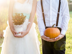 Happy young couple holding flowers and pumpkin